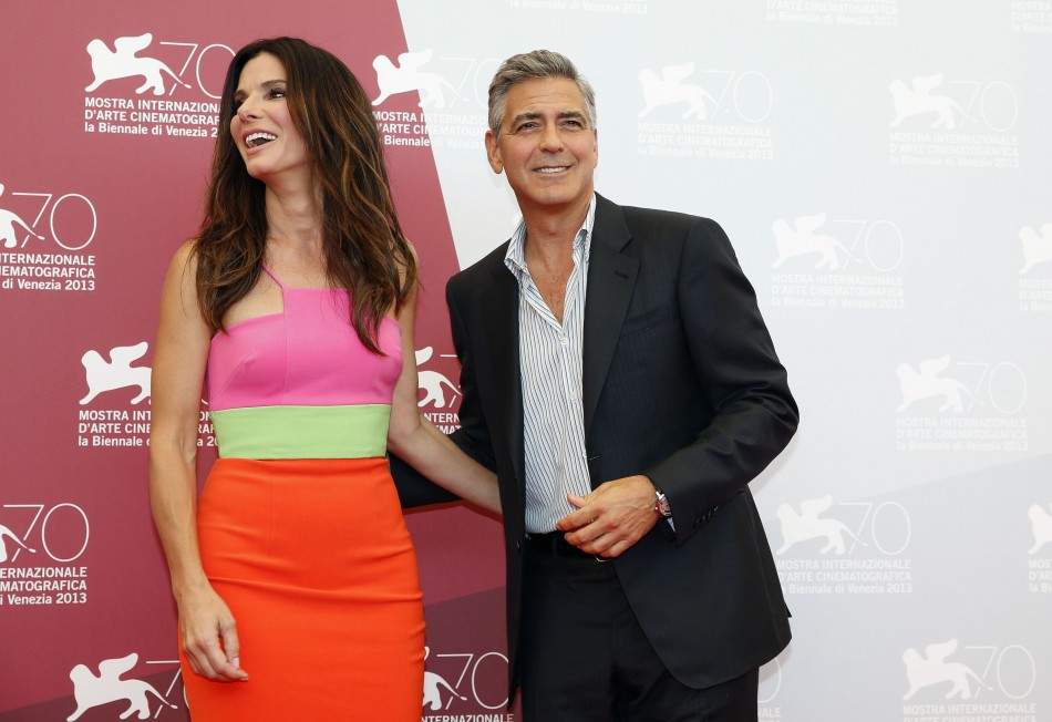 US actor George Clooney poses with actress Sandra Bullock during a photo call at the 70th Venice Film Festival in Venice August 28, 2013. Clooney and Bullock star in Alfonso Cuaron's movie Gravity, which debuts at the festival. (REUTERS/Alessandro Bianchi)