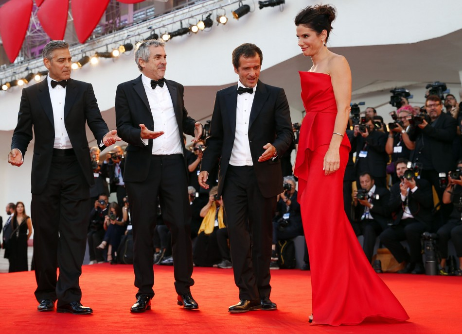 George Clooney, director Alfonso Cuaron (2nd L) and producer David Heyman (2nd R) gestures as Sandra Bullock  arrives on the red carpet for the premiere of Gravity at the 70th Venice Film Festival in Venice  2013. (REUTERS/Alessandro Bianchi)