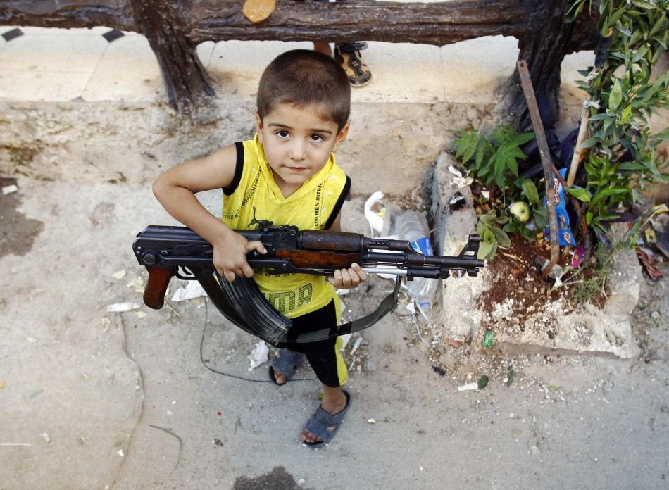 Children with guns walk the streets in war-torn Damascus PIC: Reuters