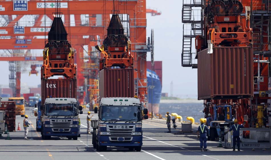 Workers load containers from trucks onto a cargo ship at a port in Tokyo