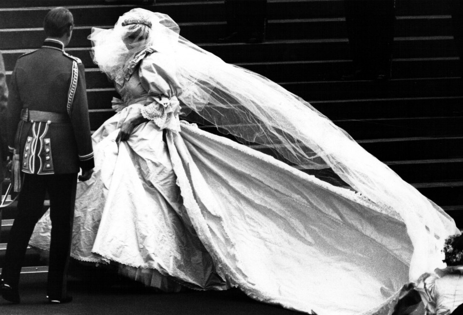 This iconic photo shows Lady Diana Spencer, soon to become the Princess of Wales, showing her wedding gown for the first time, turns as her bridesmaids set her train on arrival at Saint Paul's Cathedral for her wedding to Prince Charles in London, July 29
