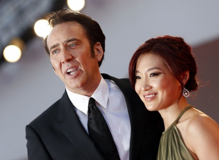 Actor Nicolas Cage and his wife Alice Kim pose during a red carpet during the 70th Venice Film Festival in Venice August 30, 2013. Cage stars in David Gordon Green's movie Joe, which debuts at the Venice Film Festival. (REUTERS/Alessandro Bianchi)