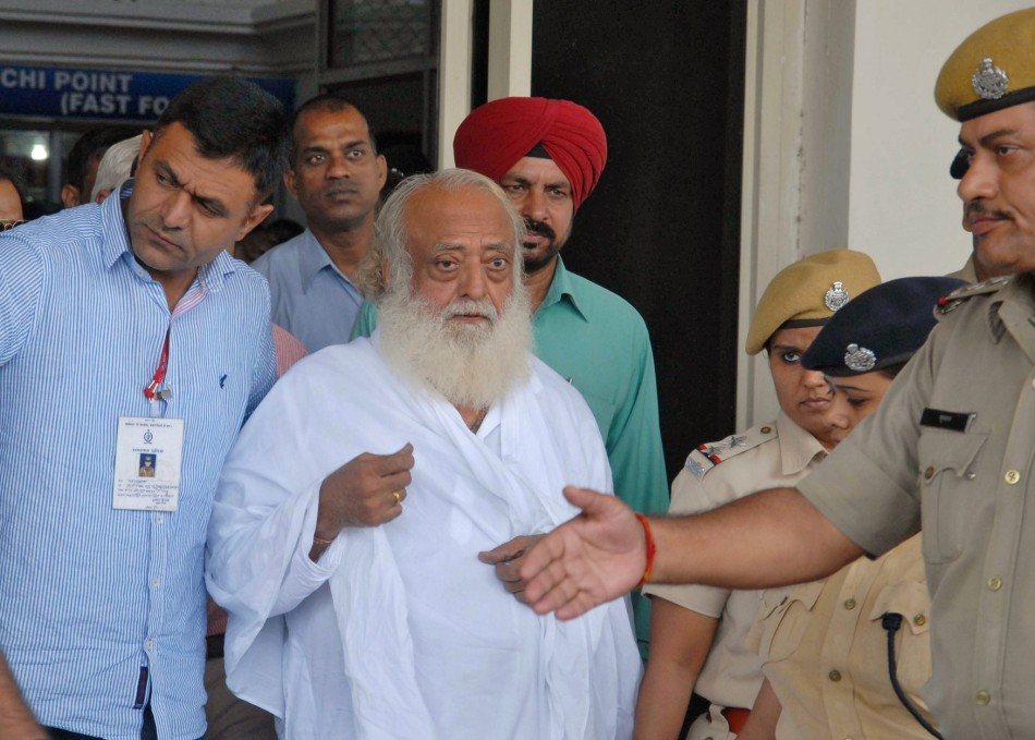 Asaram Bapu is led from Jodphur airport by police to face questioning.
