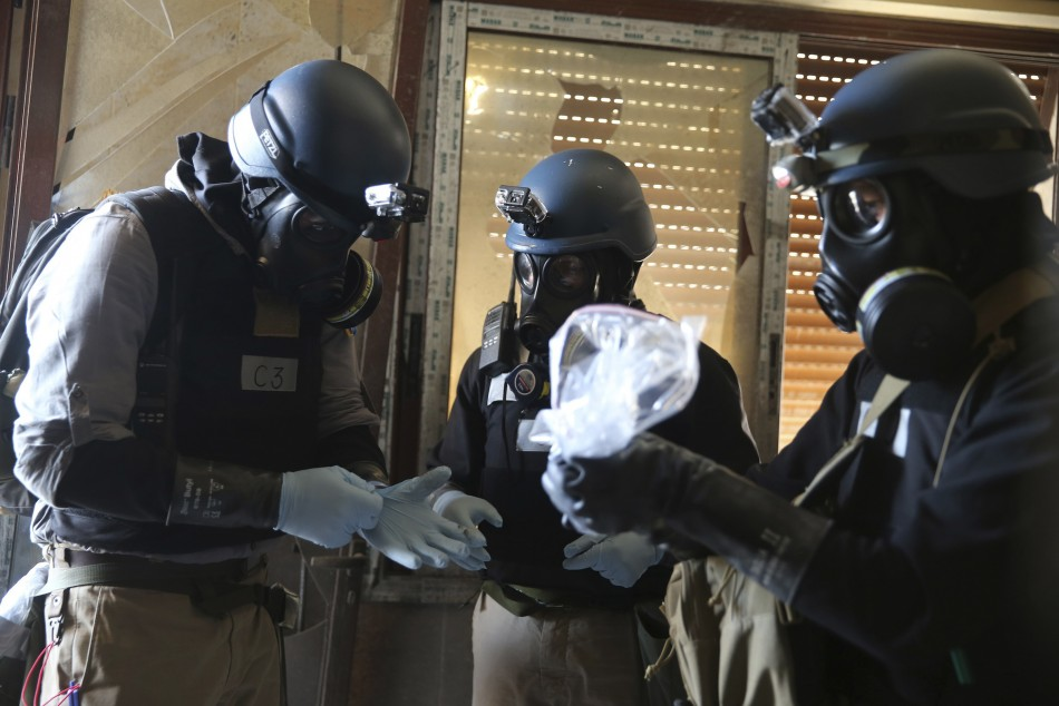 A U.N. chemical weapons expert, wearing a gas mask, holds a plastic bag containing samples from one of the sites of an alleged chemical weapons attack