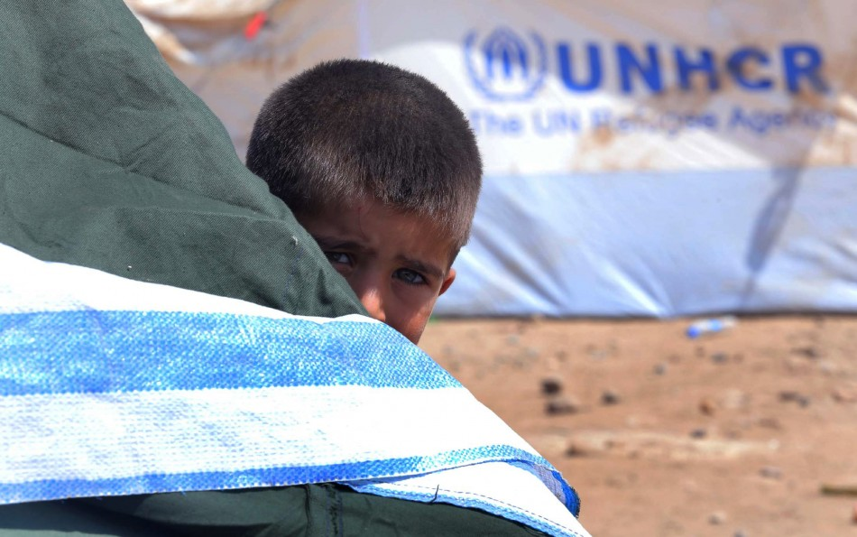 A Syrian refugee boy peeps behind a tent at the Quru Gusik refugee camp on the outskirts of Arbil in Iraq's Kurdistan region