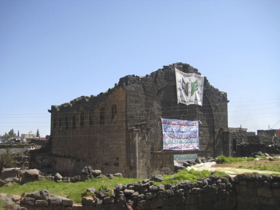 Demonstrators raise a banner, praising the Syrian Free Army battling Syrian President Bashar al-Assad along with verses from the Koran, on wall of Bosra's famous Roman ruins March 18, 2012. The ancient city structures have been damaged in the Syrian civil war. (REUTERS/Shaam News Network/Handout)