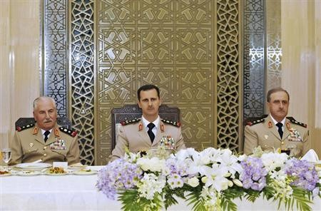 Syria's President Bashar al-Assad (C) attends a dinner in honor of the army officers on the 65th Army Foundation anniversary in Damascus August 1, 2010. On left is Syrian Defense Minister General Ali Habib
