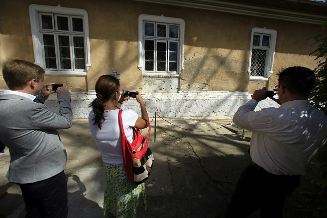 Visitors take pictures of the spot where Romania's late communist dictator Nicolae Ceausescu and his wife Elena were executed (Reuters)