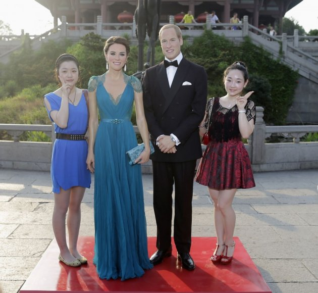 Visitors pose for photographs next to Madame Tussauds' wax figures Prince William and Catherine (2nd L), Duchess of Cambridge, in front of the Yellow Crane Tower during a promotional event in Wuhan, Hubei province August 13, 2013. The fifteenth Madame Tus