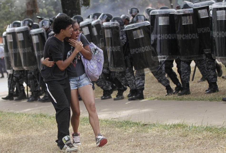 A couple attempt to flee unrest outside brasilia's mane garrincha stadium yesterday.