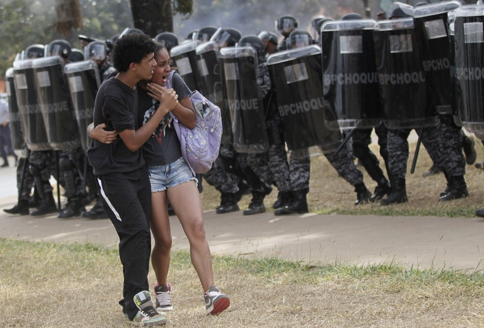 A couple attempt to flee unrest outside brasilia's mane garrincha stadium yesterday.