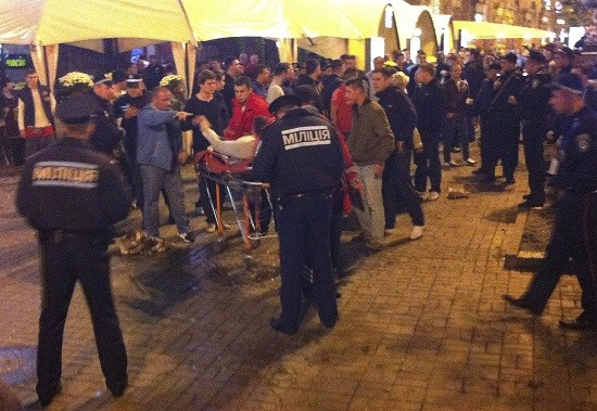 An injured English football fan lies on a stretcher and surrounded by medical personnel and police in central Kiev (Reuters)