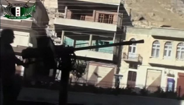 A Syrian rebel fires a heavy machine gun mounted on the back of a vehicle in Maaloula, a suburb of Damascus, in this image taken from a September 4, 2013 video footag