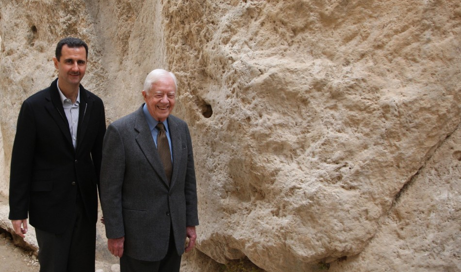 Syria's President Bashar al-Assad (L) walks with former U.S. president Jimmy Carter, at mountain pass of St. Taqla convent, during a visit to the historic city of Maaloula,