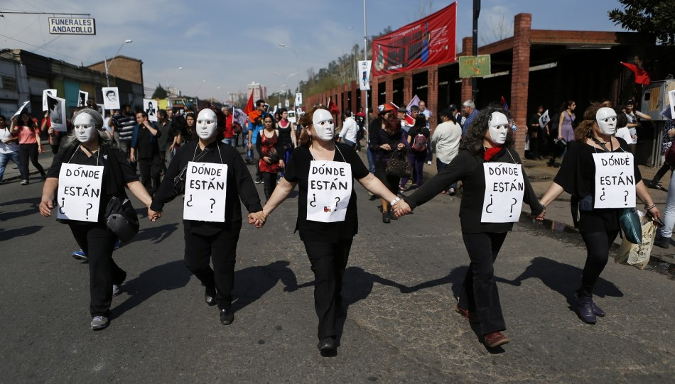 Demonstrators wearing masks and signs that read,