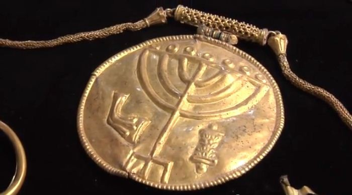 The gold medallion hangs from a gold chain and has the symbols of a menorah (centre), a shofar (left) and a Torah scroll (right) etched into it. (YouTube Video Screenshot/Hebrew University)