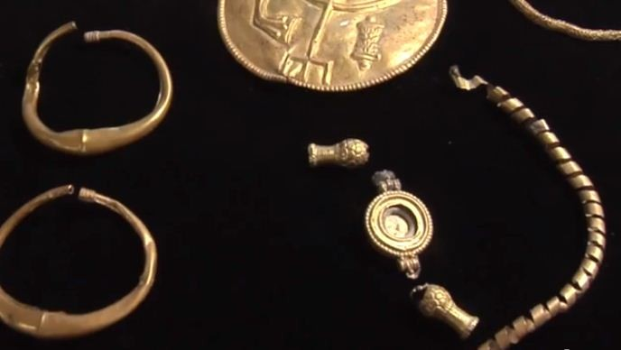 A pair of large gold earrings, a gold-plated silver hexagonal prism and a silver ingot were found along with the coins. (YouTube Video Screenshot/Hebrew University)