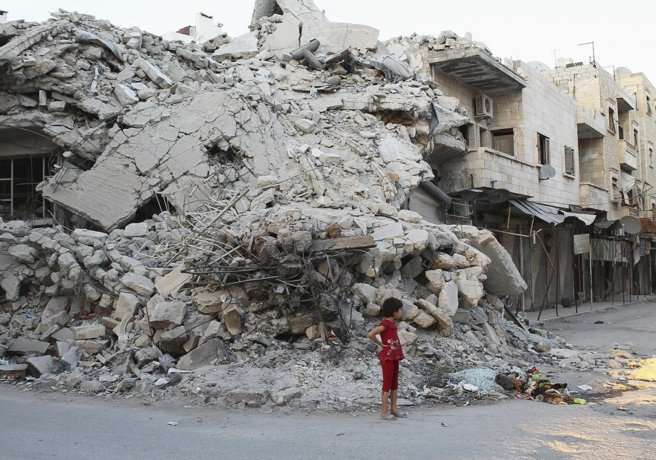 A girl stands in front of a building damaged by what activists said was shelling by forces loyal to Syria's President Bashar al-Assad