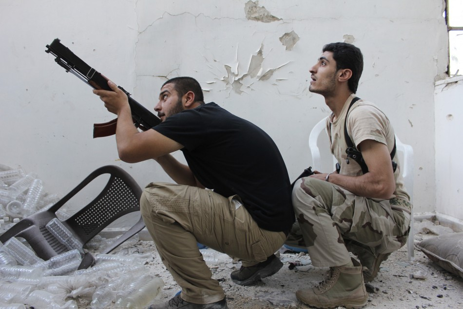 A Free Syrian Army fighter points his weapon