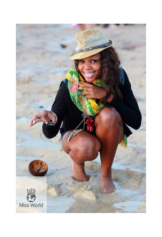 Miss World contestant smiles after baby turtles are released into the wild.