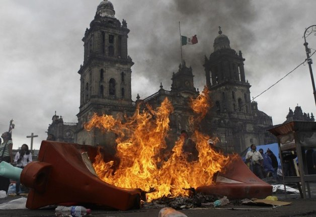 Teachers and protesters stand near a burning barricade before they are evicted from Zocalo Square by the riot police in Mexico City.