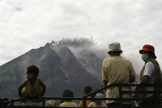 Villagers wait to be taken to safety as Mount Sinabung sends ash and smoke high into the air.
