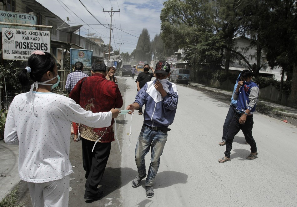 A paramedic hands out masks to people fleeing the mount Sinabung eruption.
