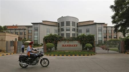 A man rides a motorcycle in front of the office of Ranbaxy Laboratories at Gurgaon, on the outskirts of New Delhi, June 13, 2013.
