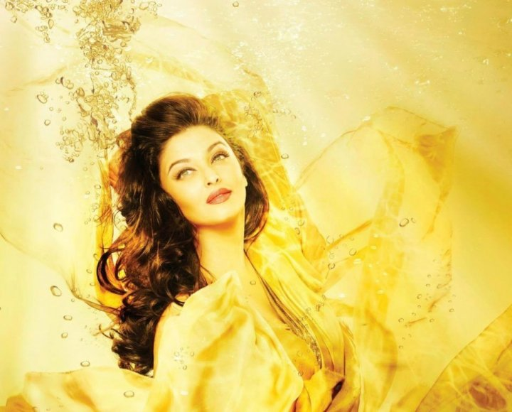 In another photo, a teaser campaign with the theme Bathe in Gold, she is seen in bright yellow hues that merge with the golden water background around her/Kalyan Jewellers/Facebook