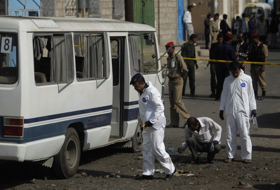 Forensic officers collect evidence at the scene of a roadside bomb attack on a military bus in Sanaa September 9, 2013