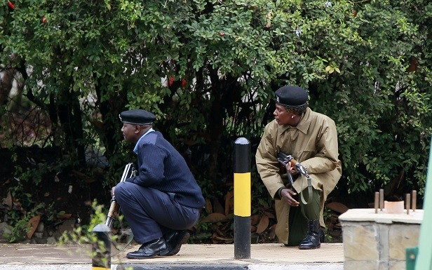 Kenyan police officers take positions during the ongoing military operation at the Westgate Shopping Centre in the capital Nairobi (Reuters)