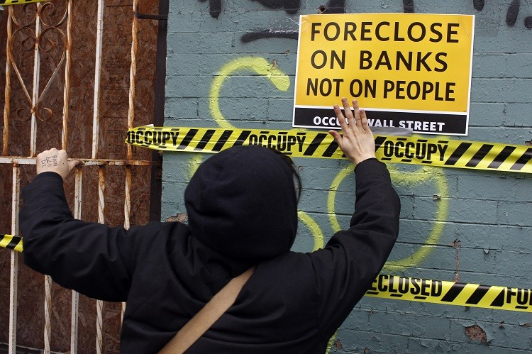 An Occupy Wall Street demonstrators pastes tape and signs to a foreclosed property in the East New York section of Brooklyn (Photo: Reuters)