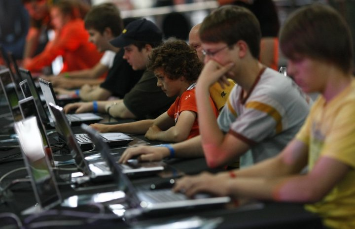 Teenagers and children at a computer games fair.