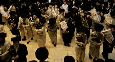 The synagogues Torah scrolls are removed from the ark and danced with during the ceremony