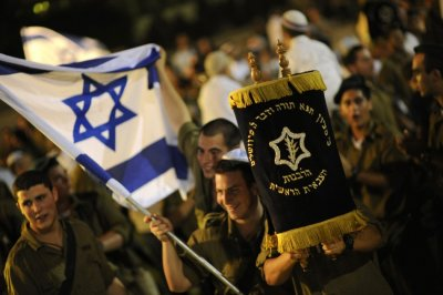 Israeli soldiers dance with Torah scrolls during the celebrations of Simchat Torah at the Eshkol regional council in the Negev