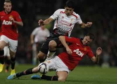Luis Suarez challenged by Jonny Evans