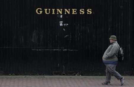 A man passes the Guinness beer factory in the city centre of Dublin (Reuters)
