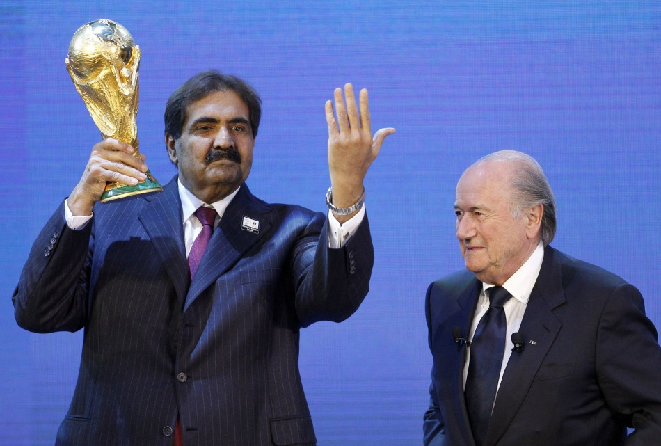 Qatar's Emir Sheikh Hamad bin Khalifa al Thani (L) holds up a copy of the World Cup he received from FIFA President Sepp Blatter PIC: Reuters