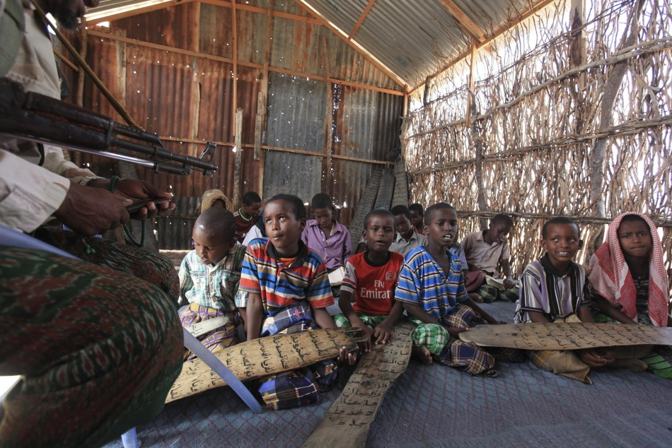 A teacher at a school in Dhusamareeb, central Somalia, takes a class while armed with an AK 47 to defend against Islamist Al-Shabaab fighters
