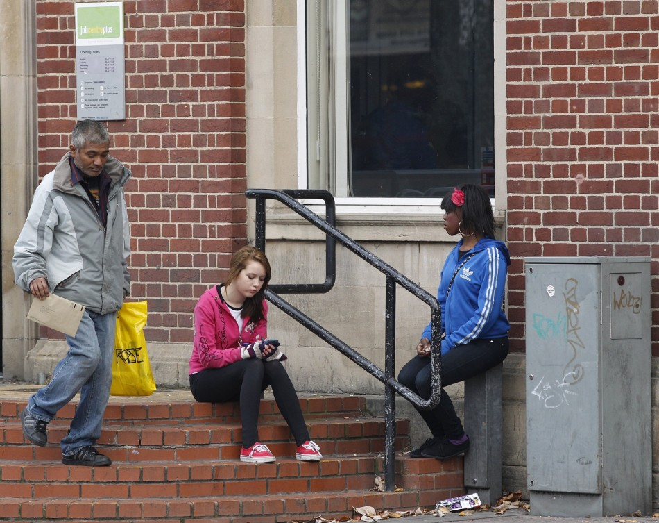A young woman checks her smartphone outside a job centre in Leicester