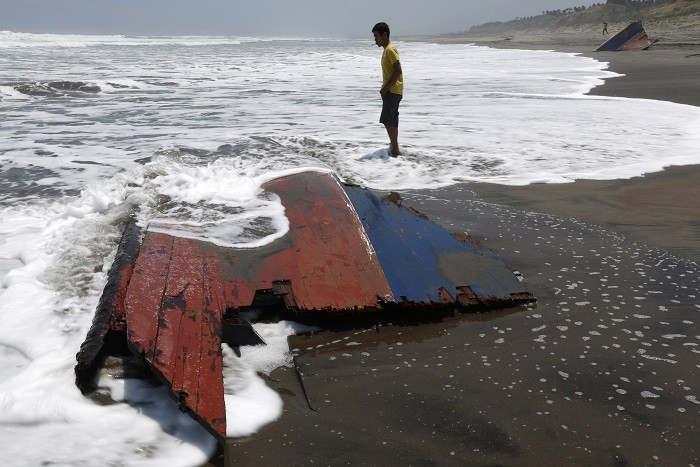 A youth stands near a piece of wreckage of a boat which sank off the Indonesian coast