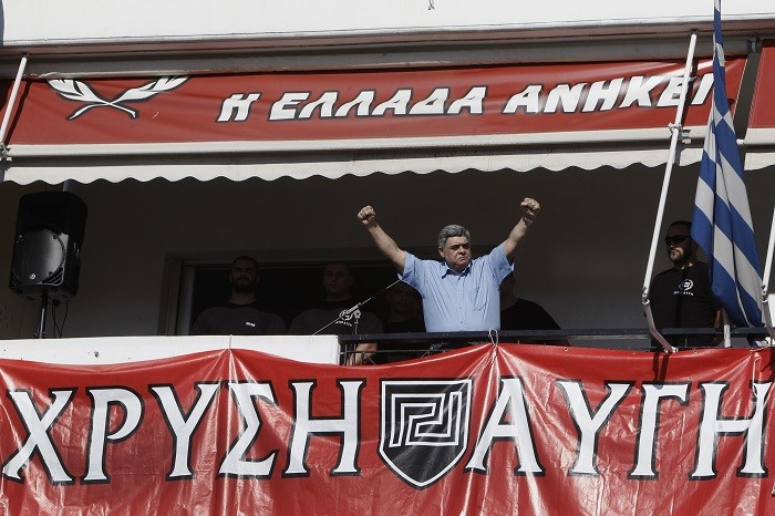 Nikolaos Michaloliakos gestures to supporters