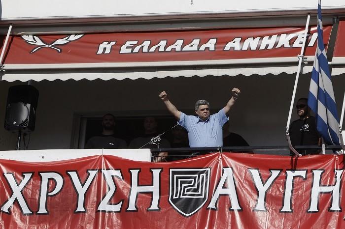 Nikolaos Michaloliakos gestures to supporters