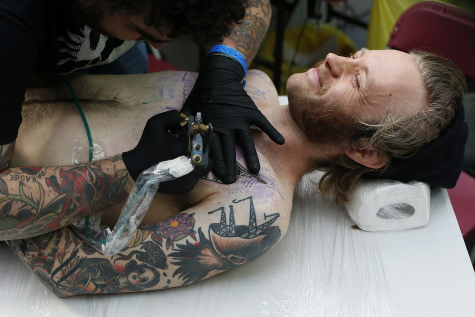 Emil Sarelind is tattooed by tattoo artists Deno (L).