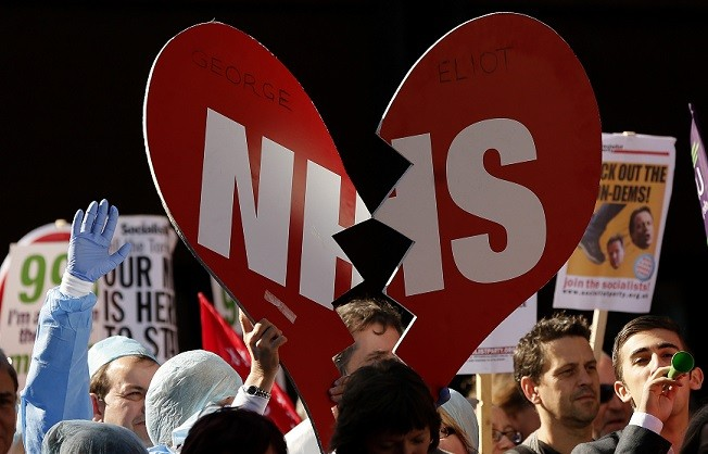 Demonstrators hold placards during a protest march on the first day of the Conservative Party annual conference in Manchester (Reuters)