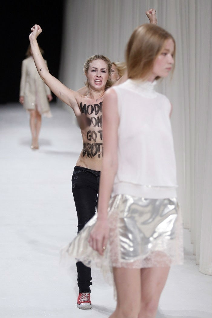 Paris Fashion Week model almost oblivious to topless Femen protest against fashion industry