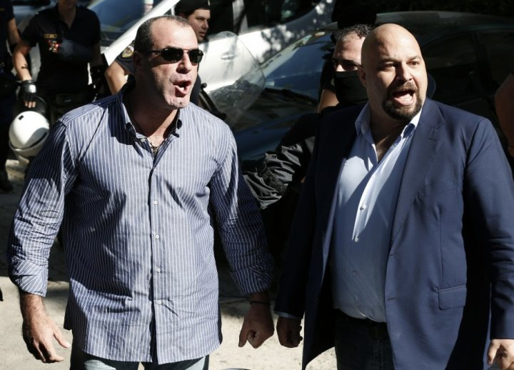 Extreme-right Golden Dawn party lawmakers Ilias Panagiotaros (R) and Nikos Michos yell at media people after being released in Athen
