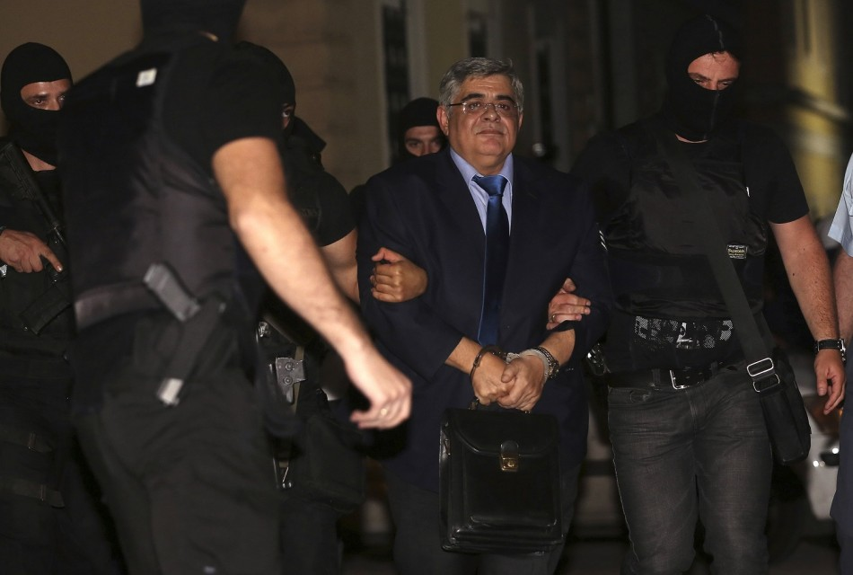 Extreme-right Golden Dawn party leader Nikolaos Michaloliakos (C) is escorted by anti-terrorism police officers into a court house in Athens