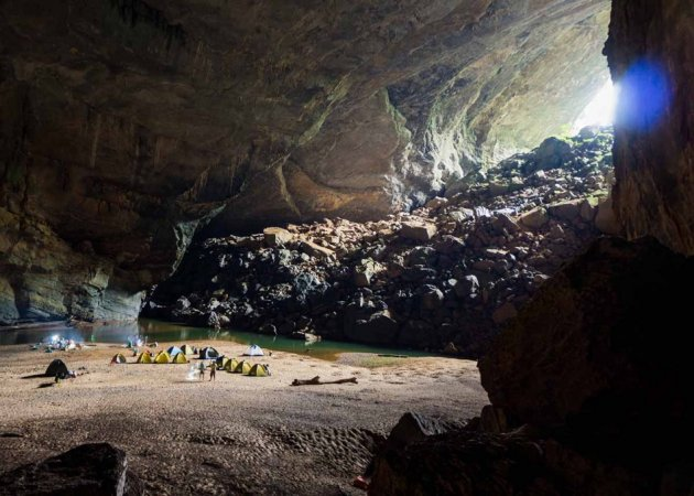 Adventure travellers camp near the river inside Vietnam's Son Doong Cave. (Photo: Oxalis)