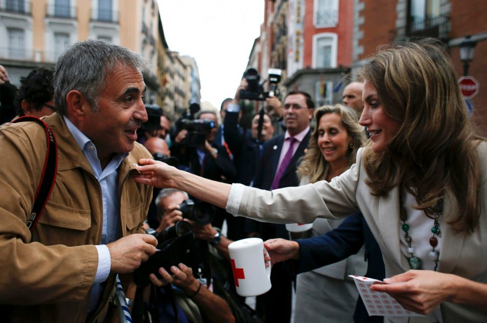 Princess Letizia puts a Red Cross sticker on the jacket of Spanish photographer Roberto Fernandeza during the event. (Photo: REUTERS/Susana Vera)